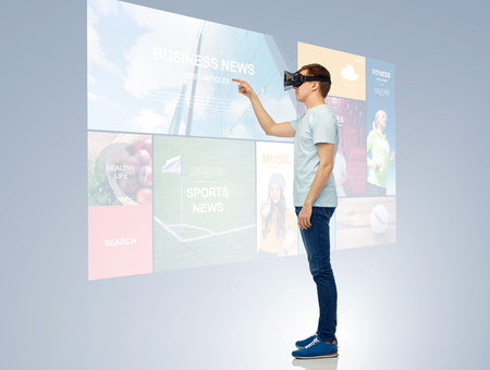 web side: 3d technology, virtual reality, entertainment, cyberspace and people concept - happy young man with virtual reality headset or 3d glasses playing game and touching screen with internet news Stock Photo