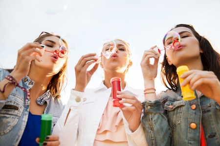 summer vacation, holidays, fun and people concept - group of happy young women or teenage girls blowing bubbles outdoors Stock Photo