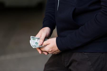 drug trafficking: drug trafficking, finances, addiction, people and sale concept - close up of addict or dealer hands with dollar money