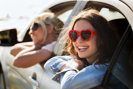 summer holidays, valentines day, travel, road trip and people concept - happy teenage girls or young women heart shaped sunglasses in car at seaside