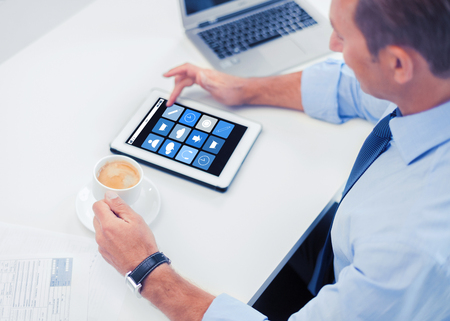 application icons: business, people and technology concept - businessman with application icons on tablet pc drinking coffee in office