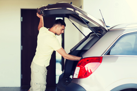 baggage: road trip, transport, private property leisure and people concept - young man with open car trunk at parking space Stock Photo