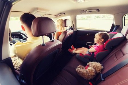 family, transport, safety, road trip and people concept - happy parents with little child driving in car Stockfoto