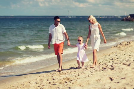 resort life: family, vacation, adoption and people concept - happy man, woman and little girl in sunglasses walking on summer beach