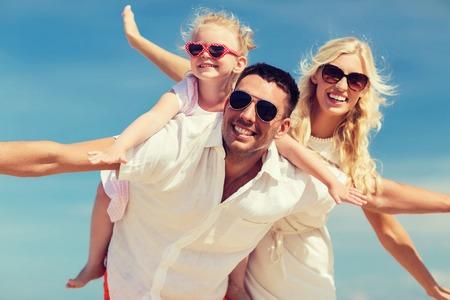 mom dad: familia, vacaciones de verano, la adopción y la gente concepto - hombre feliz, mujer y niña en gafas de sol que se divierten sobre fondo azul cielo