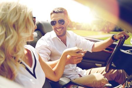 道路の旅、旅行、デート、カップルや人々 コンセプト - 幸せな男と女のカブリオレ車屋外での運転
