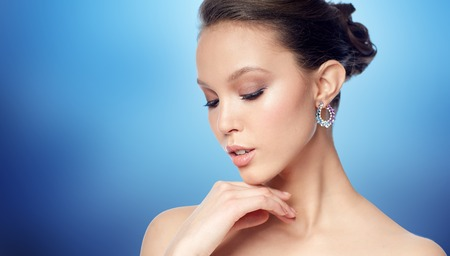 jewel: beauty, jewelry, accessories, people and luxury concept - close up of beautiful asian woman face with earring over blue background Stock Photo