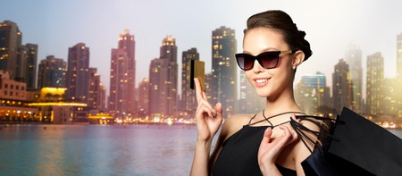 sale, finances, fashion, people and luxury concept - happy beautiful young woman in black sunglasses with credit card and shopping bags over dubai city night lights background