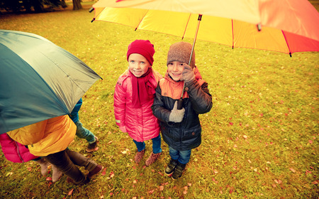 people together: childhood, friendship, season, weather and people concept - group of happy kids with umbrella in autumn park Stock Photo