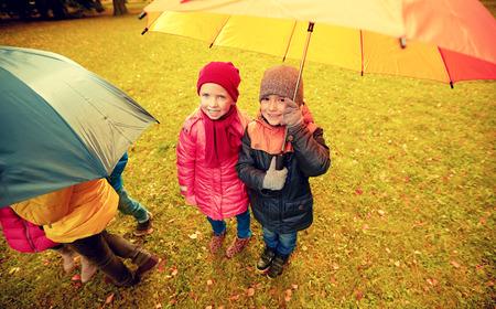personas reunidas: la infancia, la amistad, la temporada, el clima y la gente concepto - Grupo de niños felices con el paraguas en parque del otoño