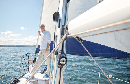 voile: sailing, age, tourism, travel and people concept - happy senior man on sail boat or yacht floating in sea
