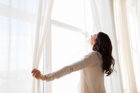 Schwangerschaft, Mutterschaft, Menschen und Konzept Erwartung - Nahaufnahme eines glücklichen schwangeren Frau öffnenden Fenster Vorhänge Standard-Bild