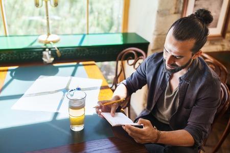 hombre escribiendo: la gente, inspiración, externo y concepto de ocio - hombre con la escritura de la cerveza para el cuaderno en el bar o pub