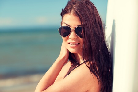 summer vacation, travel, surfing, water sport and people concept - young woman in sunglasses with surfboard on beach Stock Photo