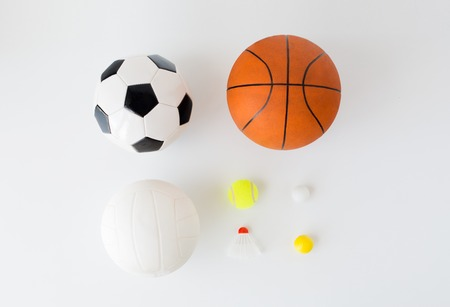 objects equipment: sport, fitness, game, sports equipment and objects concept - close up of different sports balls set and shuttlecock over white background from top