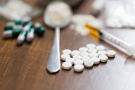 Drogenkonsum, Kriminalität, Sucht und Drogenmissbrauch Konzept - Nahaufnahme von Drogen mit Geld, Löffel und Spritze Lizenzfreie Bilder