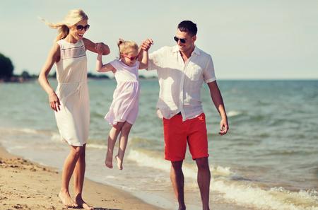 famiglia, le vacanze, l'adozione e concetto persone - uomo felice, donna e bambina in occhiali da sole che camminano sulla spiaggia di estate