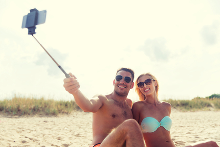 fling: love, travel, tourism, technology and people concept - smiling couple on vacation in swimwear sitting on summer beach and taking picture with smartphone selfie stick