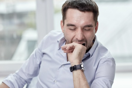 tiredness: people and tiredness concept - yawning tired man at home or office