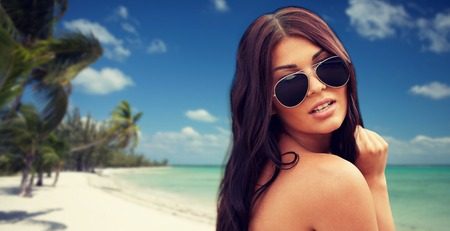 summer vacation, tourism, travel, holidays and people concept - face of young woman with sunglasses over tropical beach with palms background