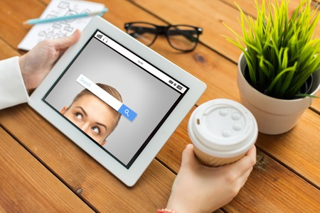 advertisement: business, education, technology, people and advertisement concept - close up of woman with internet browser search bar on tablet pc computer screen and coffee cup on wooden table Stock Photo
