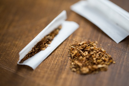 pernicious habit: drug use, substance abuse, nicotine addiction and smoking concept - close up of marijuana or tobacco with cigarette paper