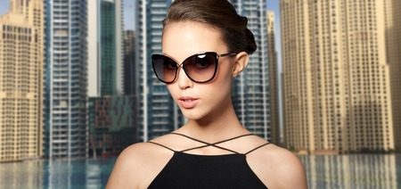 eyewear fashion: accessories, eyewear, fashion, people and luxury concept - beautiful young woman in elegant black sunglasses over dubai city street background