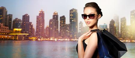 verkoop, reis, mode, mensen en luxe concept - gelukkig mooie jonge vrouw in zwarte zonnebril met boodschappentassen over dubai stadsnacht achtergrond