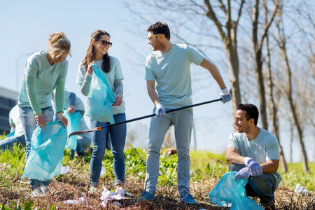 community people: volunteering, charity, cleaning, people and ecology concept - group of happy volunteers with garbage bags cleaning area in park