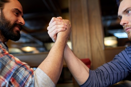 rivalry: people, leisure, challenge, competition and rivalry concept - close up of male friends arm wrestling at bar or pub