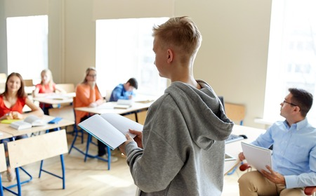public school: education, high school, learning, examination and people concept - student boy with notebook and teacher in classroom