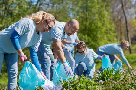 selfless: volunteering, charity, cleaning, people and ecology concept - group of happy volunteers with garbage bags cleaning area in park