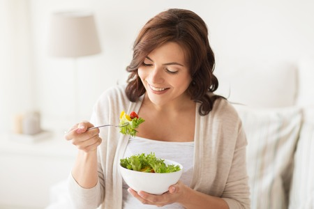 woman eat: healthy eating, dieting and people concept - smiling young woman eating vegetable salad at home