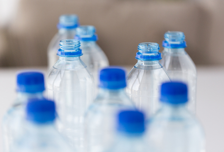 food storage: recycling, healthy eating, industry, packing and food storage concept - close up of plastic bottles with pure drinking water