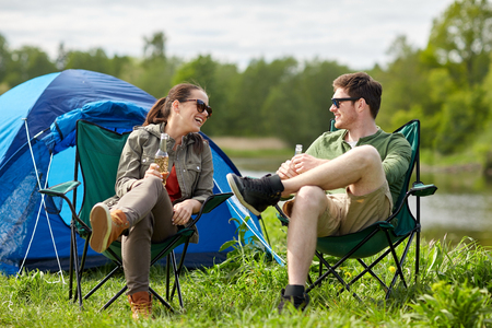 nonalcoholic beer: camping, travel, tourism, hike and people concept - happy couple drinking beer or cider at campsite tent