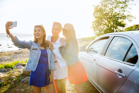 summer vacation, holidays, travel, road trip and people concept - happy teenage girls or young women with smartphone taking selfie near car at seaside Stock Photo