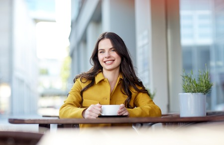 dranken en mensenconcept - gelukkige jonge vrouw of tiener met kop het drinken cacao bij het terras van de stadsstraatkoffie Stockfoto