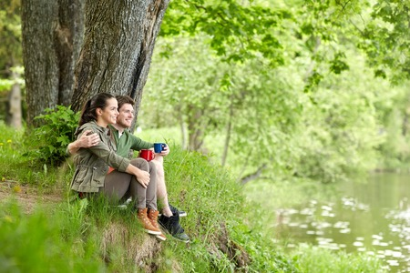 travel, tourism, hike, camping and people concept - happy couple with cups drinking tea and hugging in nature on river bank