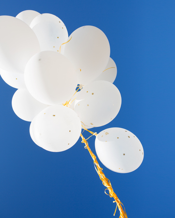 inflated: holidays, birthday, party and decoration concept - close up of inflated white helium balloons in blue sky
