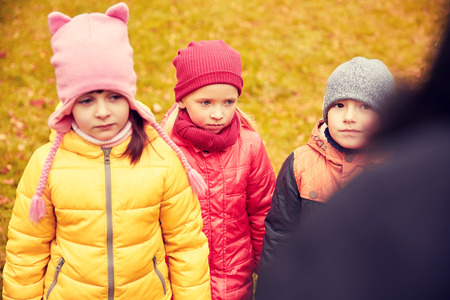 disobedience: childhood, leisure, friendship and people concept - group of sad kids being blamed for misbehavior in autumn park
