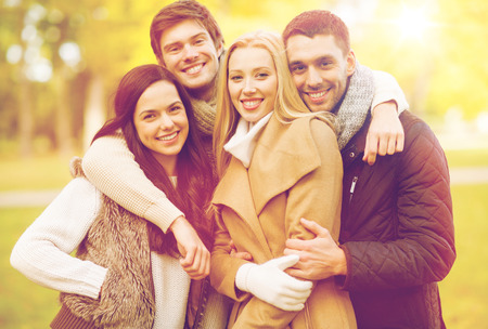 summer, holidays, vacation, happy people concept - group of friends or couples having fun in autumn park Stock Photo