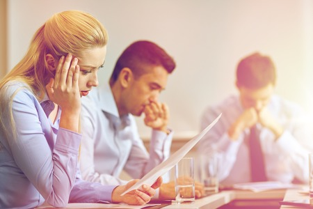 group of workers: business, teamwork, people and crisis concept - business team sitting sad and solving problem in office