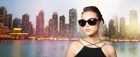 eyewear fashion: accessories, eyewear, fashion, people and luxury concept - beautiful young woman in elegant black sunglasses over dubai city night lights background