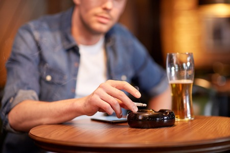 alcohols: people, nicotine addiction and bad habits concept - close up of man drinking beer, smoking cigarette and shaking ashes to ashtray at bar or pub