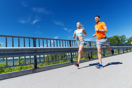 fitness, sport, friendship and healthy lifestyle concept - smiling couple with heart-rate watch running at summer seaside Stock Photo