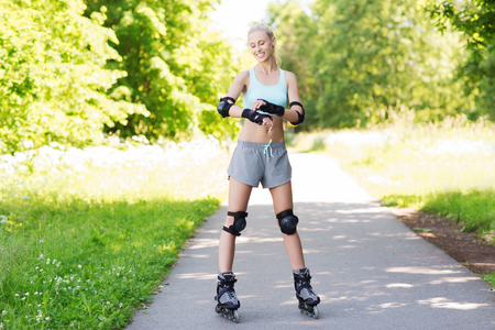 rollerblades: fitness, sport, summer, rollerblading and healthy lifestyle concept - happy young woman in rollerblades and protective gear riding outdoors