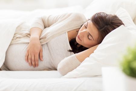 sono: gravidez, descanso, pessoas e conceito expectativa - mulher gravida feliz que dorme na cama em casa
