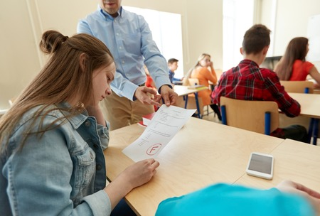 Bildung, Gymnasium, Lernen und Menschen Konzept - stören Student Mädchen mit schlechten Testergebnis und Lehrer im Klassenzimmer Standard-Bild