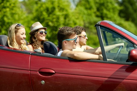 family and friends: leisure, road trip, travel and people concept - happy friends driving in cabriolet car along country road
