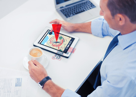 gprs: business, people, technology and navigation concept - businessman with gps navigator map on tablet pc screen drinking coffee in office